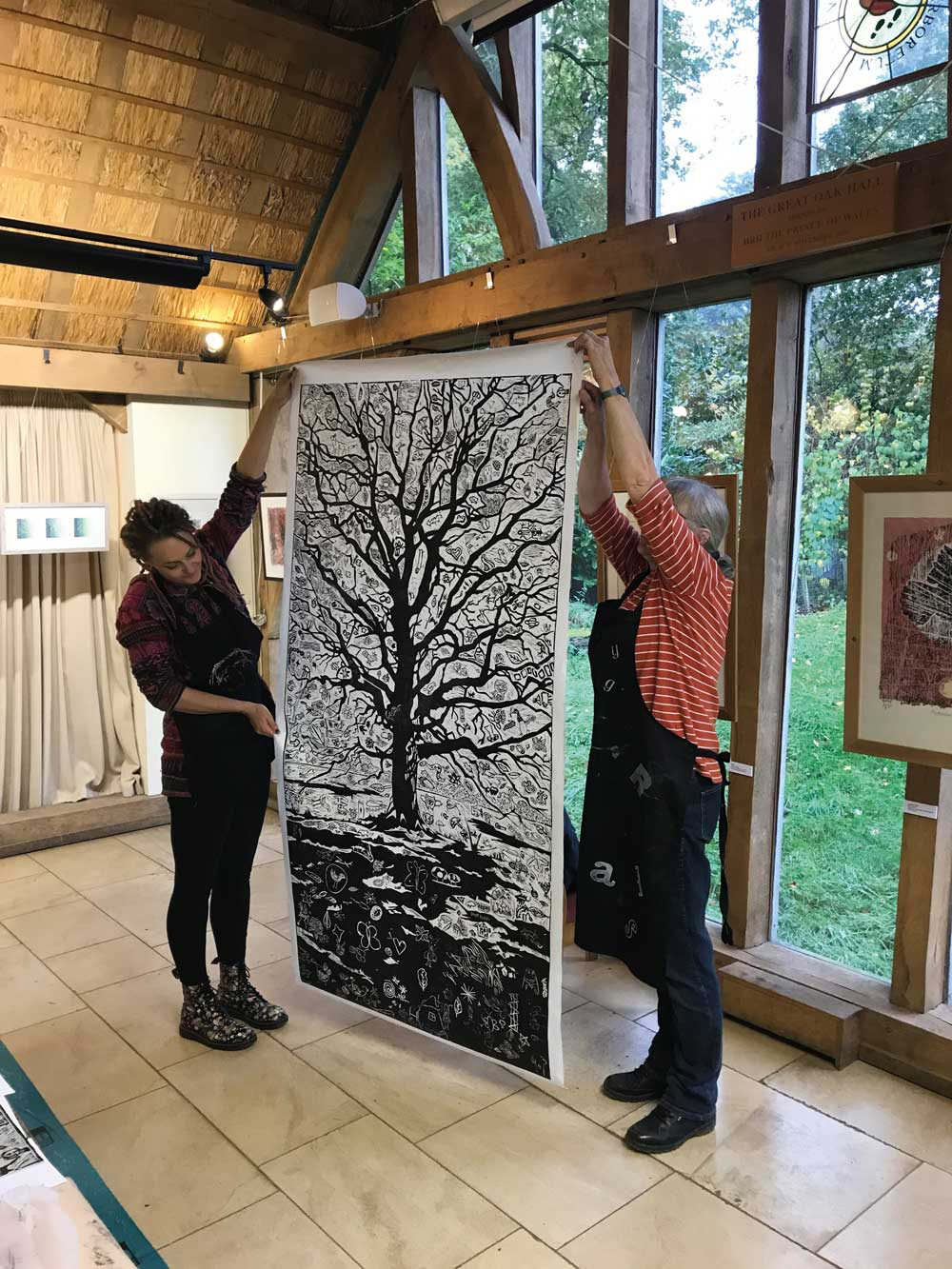 Lino print of a winter oak tree being held up