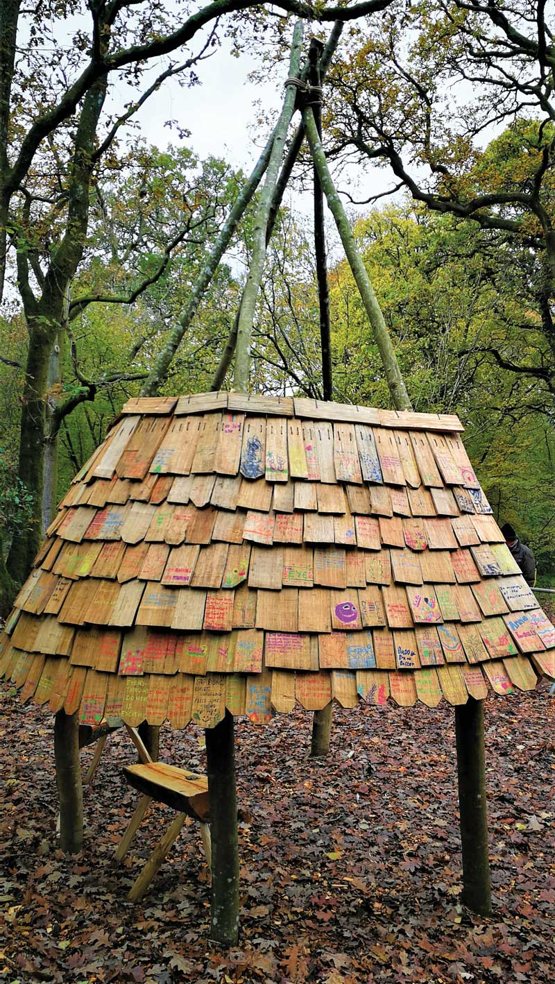 Shingle shelter structure similar to a tipi with shingle tiles decorated with quotes and thoughts